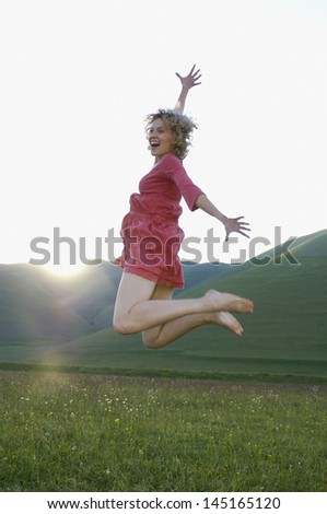 Excited young woman jumping while screaming in park - stock photo