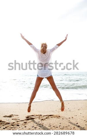 Excited young woman jumping with hands raised on beach - stock photo