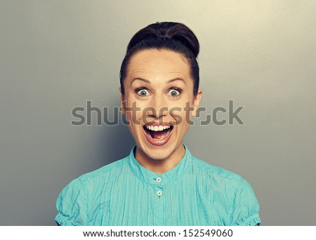 excited young woman looking at camera - stock photo