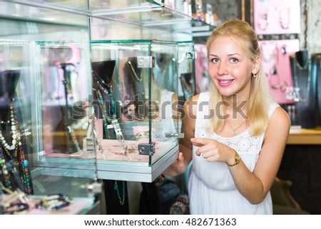 excited young woman looking at glamour accessories and bijouterie at glass showcase in store