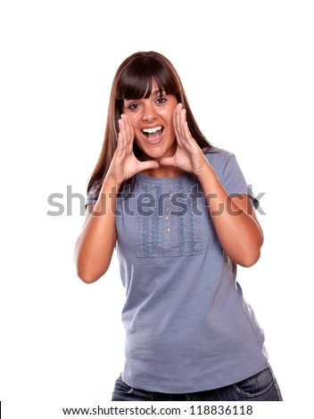 Excited young woman screaming at you on blue shirt against white background