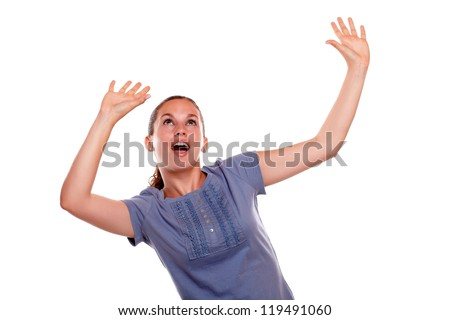Excited young woman screaming with hands up on blue shirt against white background - copyspace - stock photo