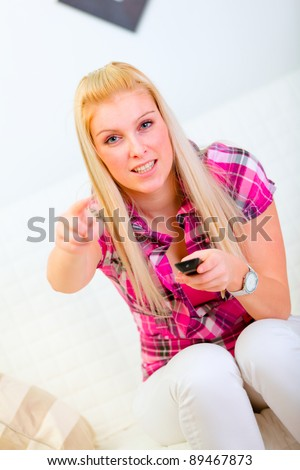 Excited young woman sitting on couch with TV remote control and pointing in camera