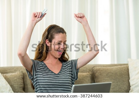 Excited young woman sitting on sofa and shopping online with a credit card