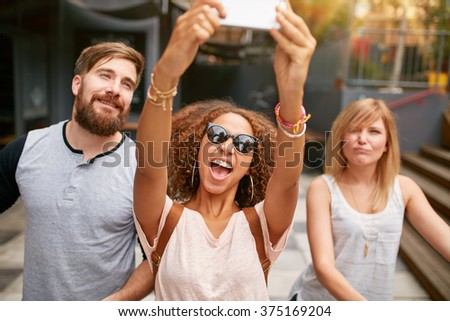 Excited young woman with friends taking a selfie on her smart phone. African woman taking selfie with mobile phone. - stock photo