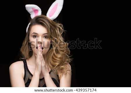 Excitement around the corner. Shot of a gorgeous curly haired young beautiful woman wearing bunny ears looking shocked on black background copyspace on the side - stock photo