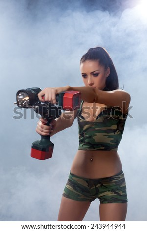 Exciting brunette posing with flashlight and drill