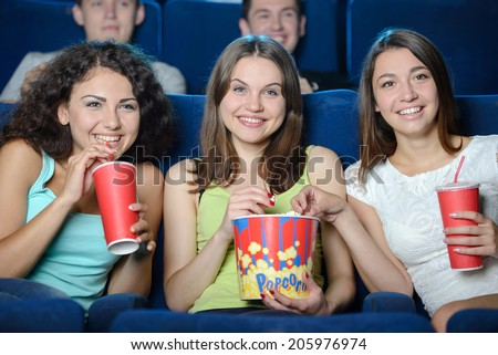 Exciting movie. Young people eating popcorn and drinking soda while watching movie at the cinema - stock photo