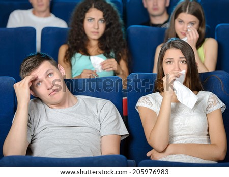 Exciting movie. Young people eating popcorn and drinking soda while watching movie at the cinema