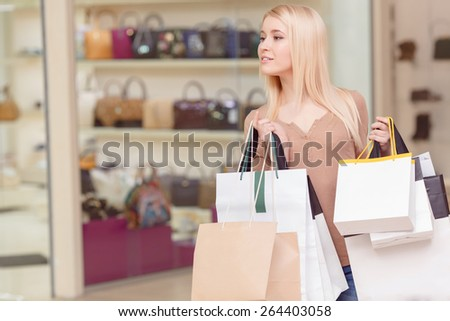 Exciting world of shopping. Beautiful young blond woman looking with curiosity somewhere and holding shopping bags - stock photo