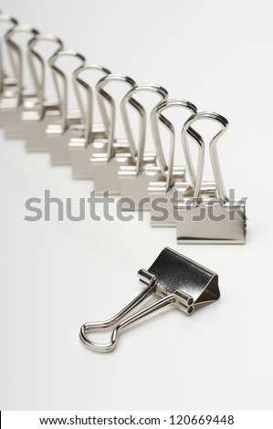 Excluded chrome clip with row of binders over white background - stock photo