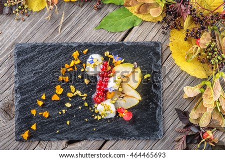 exclusive autumn cream dessert with pears, currants and pistachios on black board, decorated with flowers petals, product photography for restaurant
