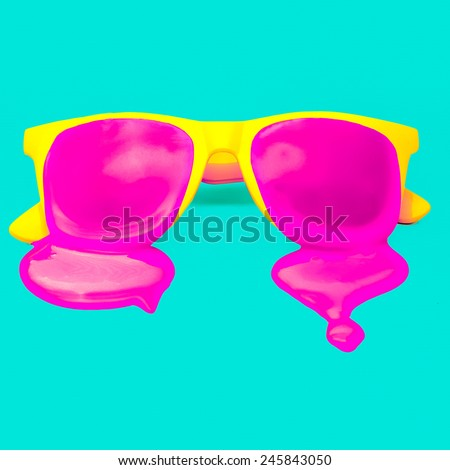 Exclusive yellow hipster sunglasses on blue background. dripping pink paint. explosion summer colors - stock photo