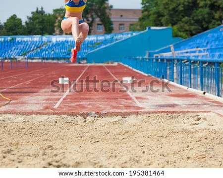 execution of the triple jump, sports background - stock photo