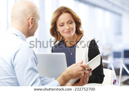 Executive broker holding tablet while presenting plan to middle age business woman. Business meeting. - stock photo