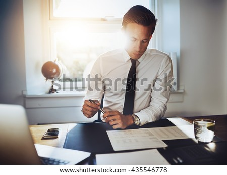 Executive business man working at desk in a classic office while wearing a suit and tie - stock photo