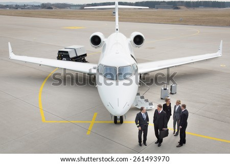 executive business team in front of corporate jet talking to pilot - stock photo