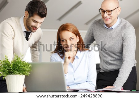 Executive business woman and her colleagues analyzing financial data on laptop. Teamwork at office.  - stock photo