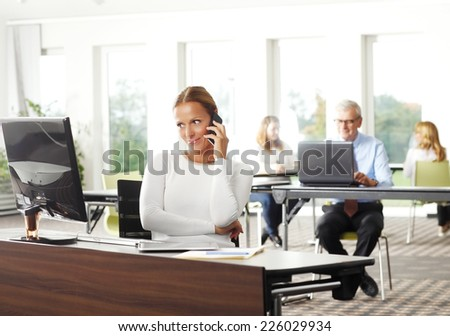 Executive business woman using mobile phone while working at office. Business people.  - stock photo