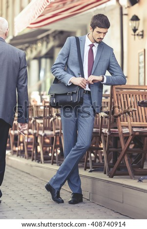 Executive businessman walking by street and watching time near french cafe at the early morning. Urban, city life. Breakfast time! - stock photo
