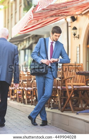 Executive businessman walking by street and watching time near french cafe at the early morning. Out of office. Urban, city life. Breakfast time! - stock photo