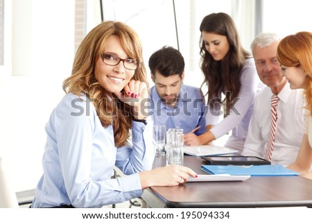 Executive businesswoman smiling at meeting. Background with colleagues.  - stock photo