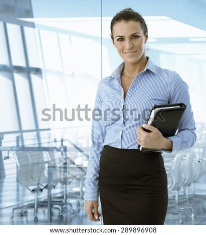 Executive caucasian businesswoman standing in front of meeting room, smiling. - stock photo