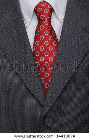 Executive dressed in business attire, red silk tie and grey wool suit - stock photo