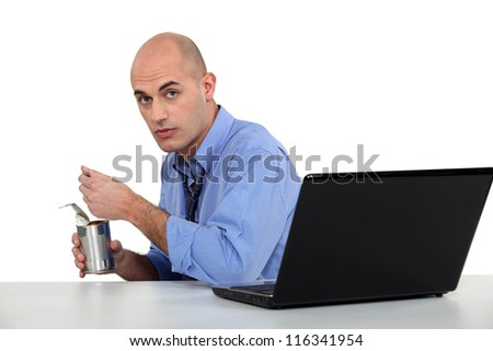 executive eating out of tin can - stock photo