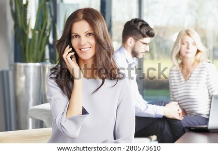 Executive female making call while sitting at office. Business people sitting at background and consulting from business plan.