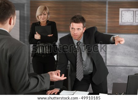 Executive firing employee in office, pointing out of frame. - stock photo