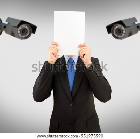 executive holding a placard in front of his face with spy cameras behind him with gray background