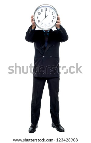 Executive holding up wall clock in front of his face. Clock striking 12. - stock photo
