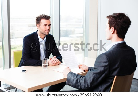Executive interviewing a young man in an office