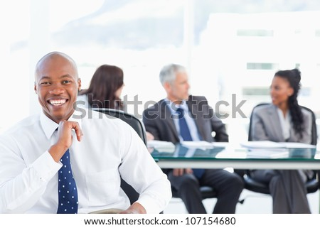Executive laughing while looking at the camera with his team in the background - stock photo