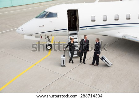 executive manager in front of corporate jet - stock photo