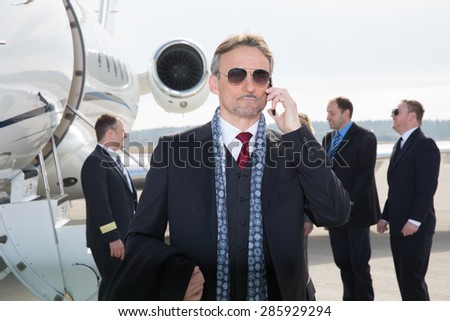 executive manager in front of corporate jet using a smartphone - stock photo