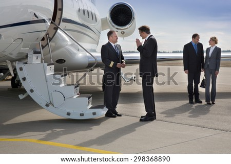 executive manager instructing pilot of corporate jet - stock photo