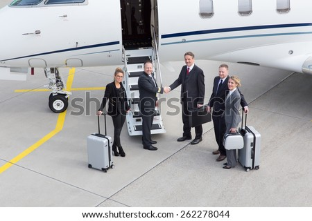 executive manager leaving corporate jet handshake with pilot - stock photo