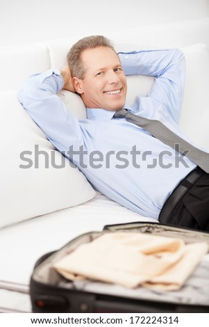 Executive on the go. Cheerful grey hair man in shirt and tie lying on bed and smiling at camera - stock photo