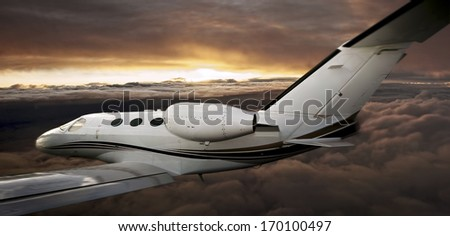 Executive plane flying between clouds at sunset