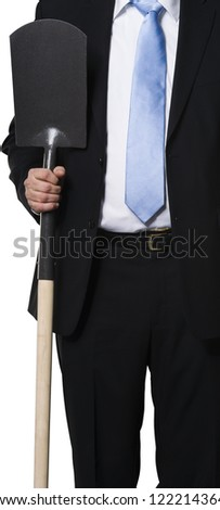 Executive showing a spade as a metaphor for digging, hard work and earth moving - stock photo