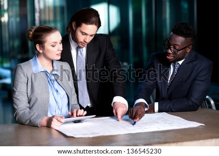 Executive team reviewing their business project together in office. - stock photo
