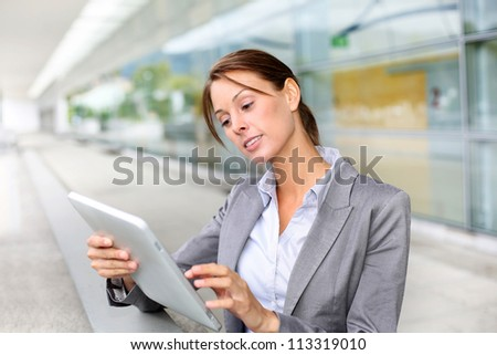 Executive woman standing outside with digital tablet - stock photo