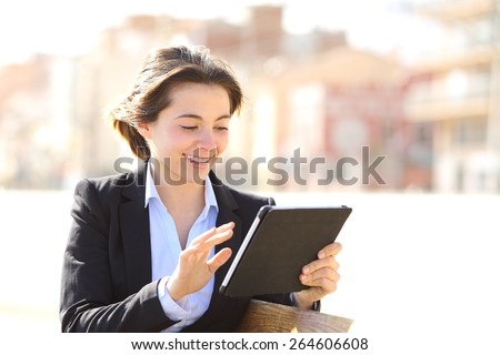 Executive working browsing a tablet in a park sitting in a bench - stock photo
