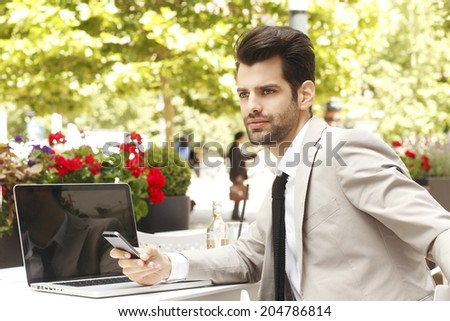 Executive young businessman sitting in coffee shop, while using his mobile. Small business.