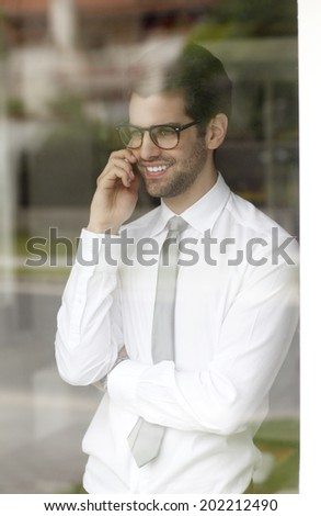 Executive young businessman standing behind window while using his smart phone.  Small Business. - stock photo