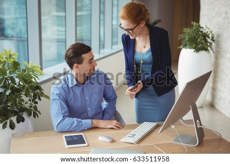 Executives discussing over mobile phone at desk in office