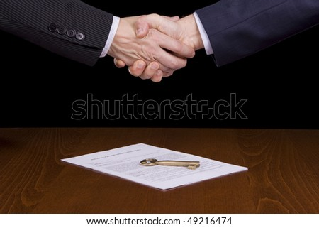 Executives handshake over a contract and a golden key - stock photo