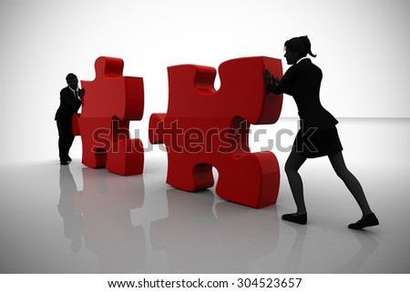 Executives placing jigsaw puzzle pieces in teamwork. A team of two executives placing jigsaw puzzle pieces into position demonstrate teamwork .